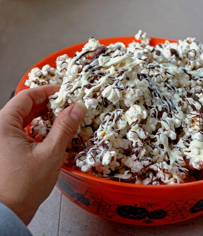 hand grabbing a piece of dark and white chocolate covered popcorn out of a bowl