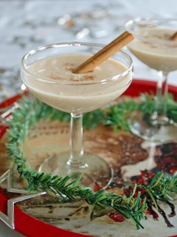 Coquito (Coconut-Rum Drink) in a martini glass with cinnamon stick