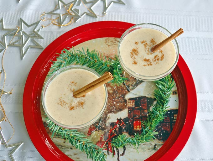 overhead view of two martini glasses of Coquito (Coconut-Rum Drink) with cinnamon sticks