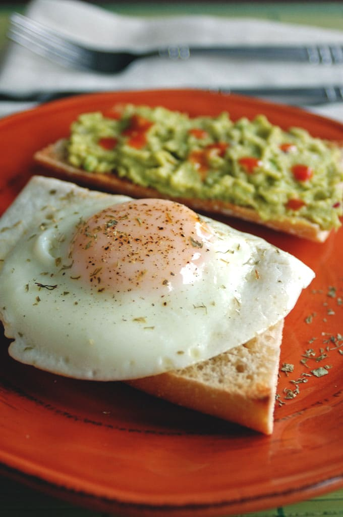 cooked egg on bread with guacamole