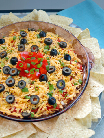 glass container of 7-Layer Taco Dip with tortilla chips