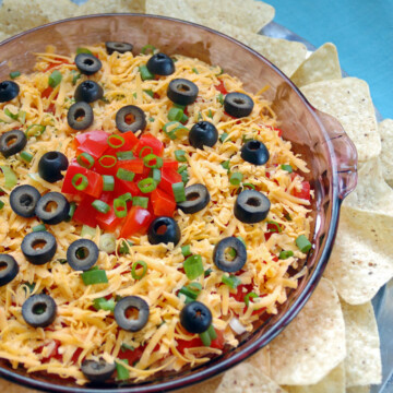 7-Layer Taco Dip in a glass container surrounded by tortilla chips