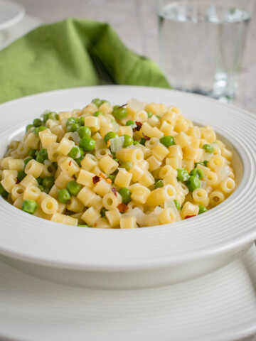 close-up photo of a bowl of pasta e piselli (pasta with peas)