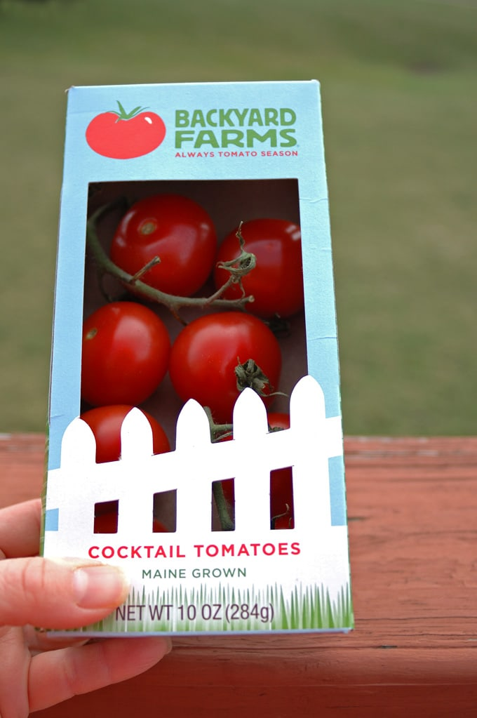 hand holding a box of Backyard Farms Tomatoes