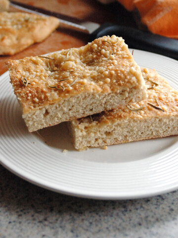 two pieces of Parmesan Focaccia with Rosemary and Garlic stacked on a plate