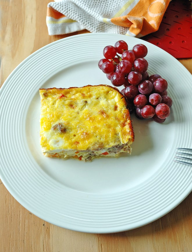 overhead view of a piece of Sausage and Peppers Breakfast Casserole on a plate with grapes