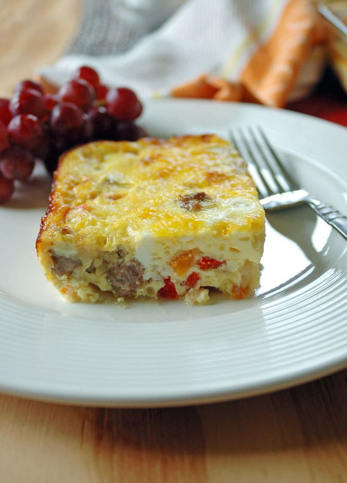 close-up of a slice of Sausage and Peppers Breakfast Casserole on a plate with fork and grapes