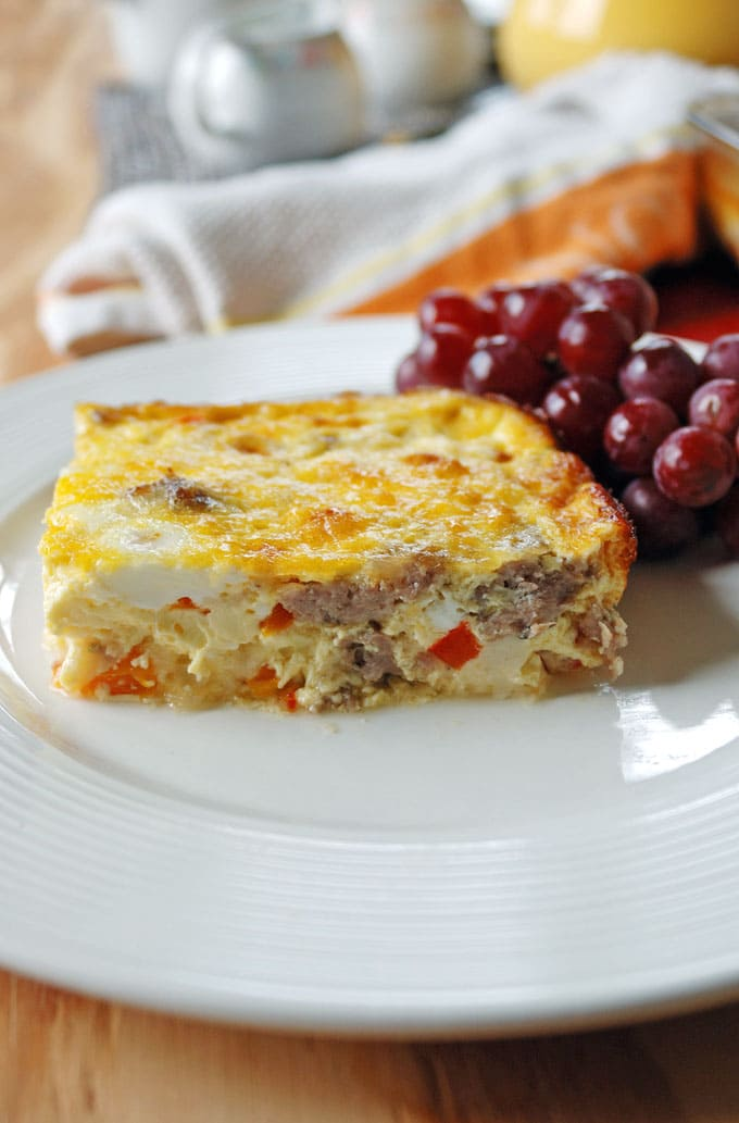 close-up photo of a plate with a piece of Sausage and Peppers Breakfast Casserole and grapes