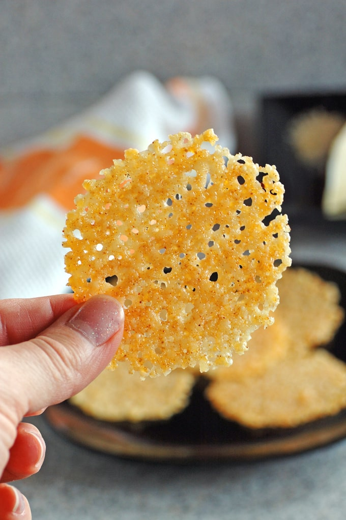 Parmesan crisp being held between thumb and finger