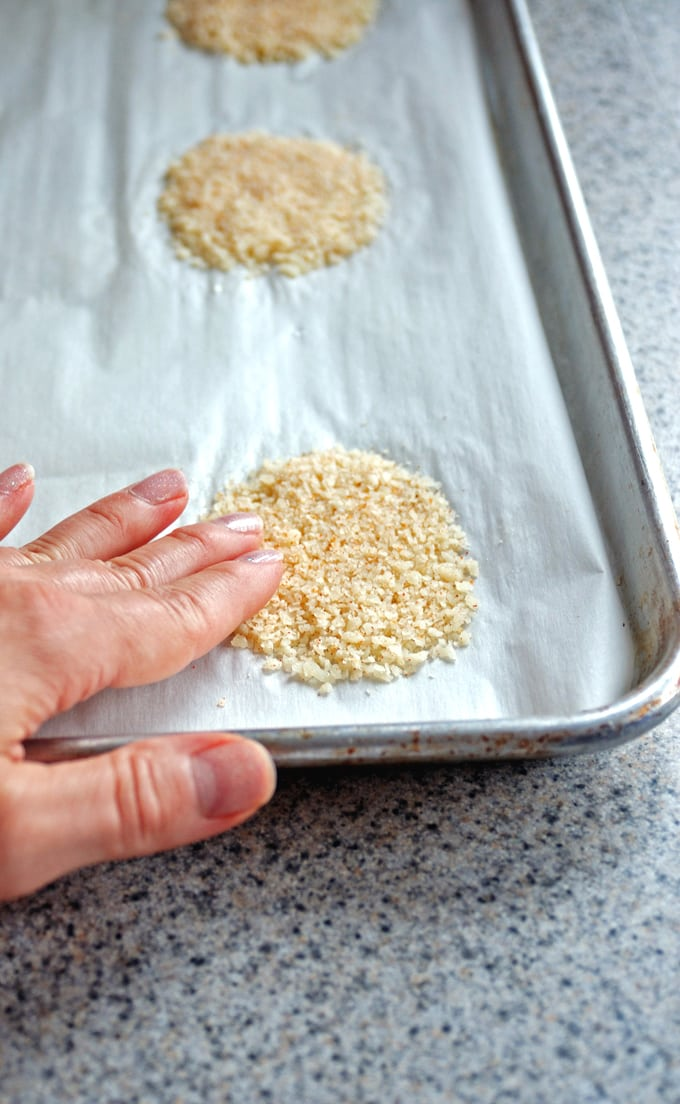 parchment-lined sheet pan with circles of grated Parmesan, hand patting one