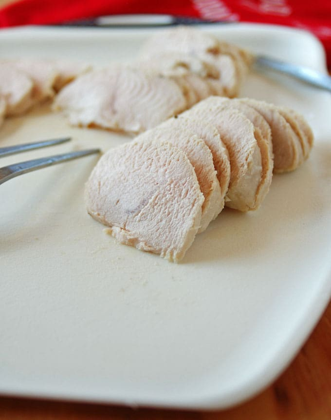 sliced turkey on a plate with a carving fork