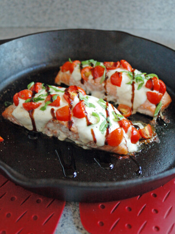 close-up of cast-iron skillet with two pieces of Salmon Caprese with Balsamic Glaze