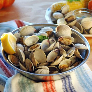 Bowl of uncooked littleneck clams with lemon