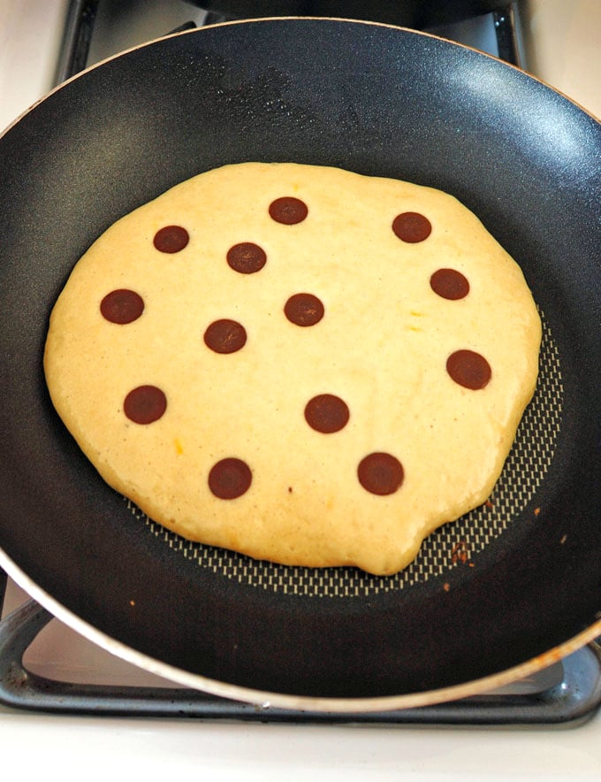 chocolate chip pancake cooking in pan on stove