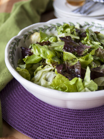 bowl of Italian green salad with homemade dressing and a napkin