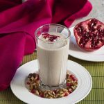 Pomegranate Smoothie with Banana and Walnuts in a glass surrounded by pomegranate and walnuts