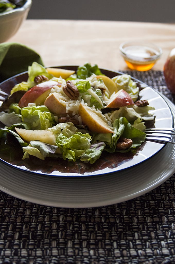 side view of a bowl of Apple Mozzarella Pecan Salad with Maple Vinaigrette and fork