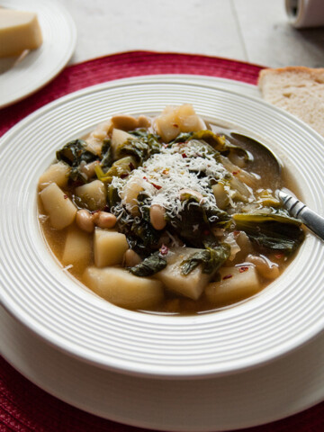 close-up of Tuscan white bean soup with escarole and potatoes in a bowl