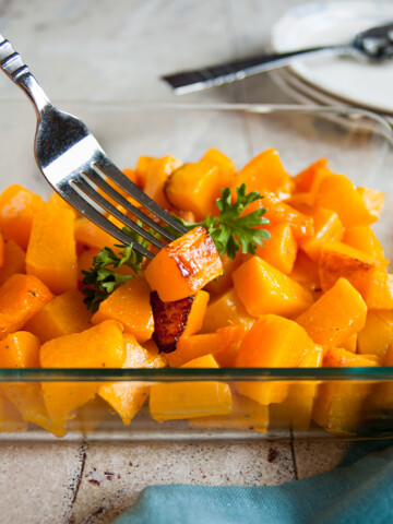 Roasted butternut squash cubes in a pan with a fork