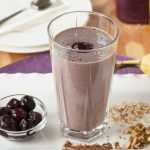 glass of chocolate-covered cherry almond smoothie surrounded by cherries, cocoa, walnuts and oats