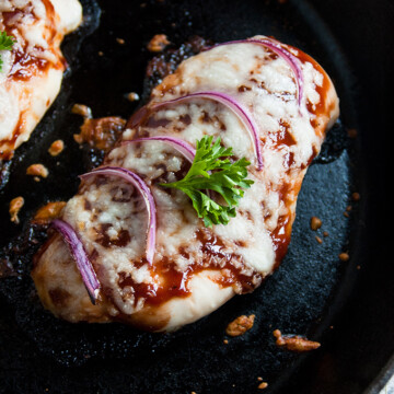 overhead view of cheesy baked BBQ chicken breasts in a skillet