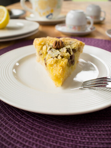 slice of lemon pie with pecans on a plate with a fork