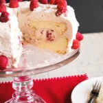 cake stand holding Raspberry-Almond Angel Food Cake with a wedge removed