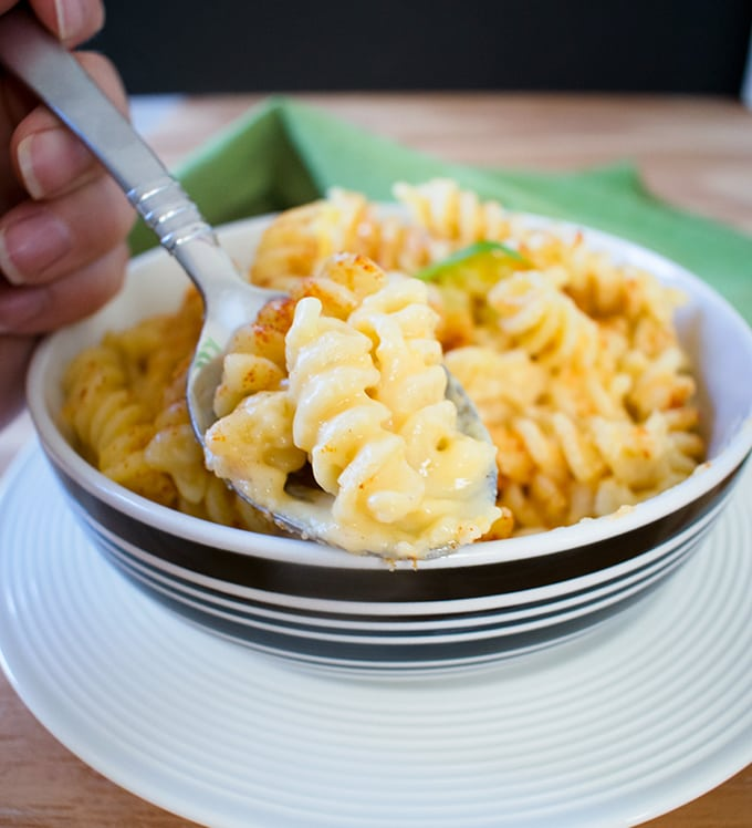 hand holding a spoonful of italian mac n cheese in front of a bowl of it to show texture