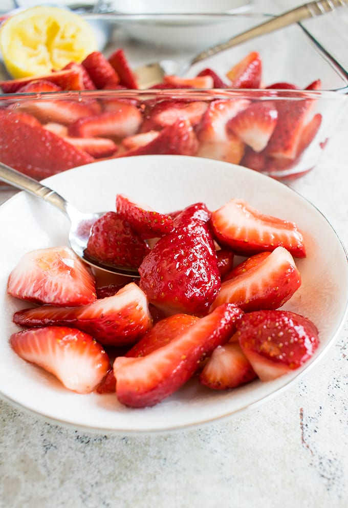 Italian Strawberries with Sugar and Lemon in a bowl with a spoon, pan of Strawberries with Sugar and Lemon behind the bowl
