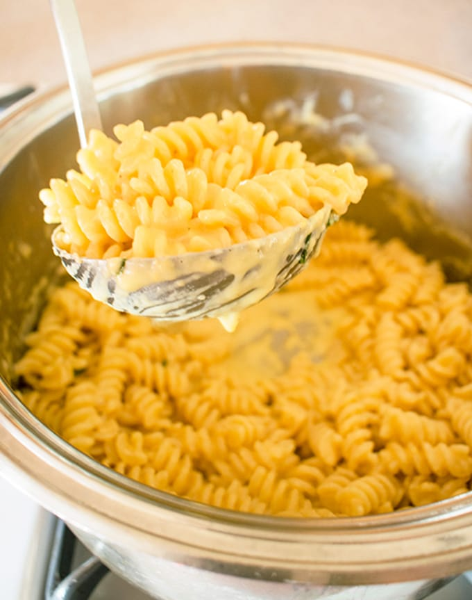 Ladle of Italian mac n cheese in front of the pot
