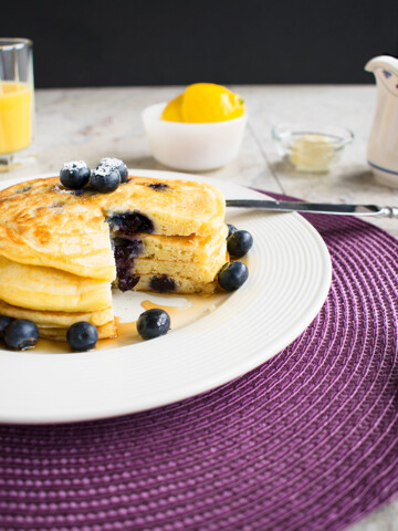 stack of lemon-blueberry pancakes with a wedge removed