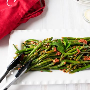 Italian green beans with tomatoes on a platter with tongs