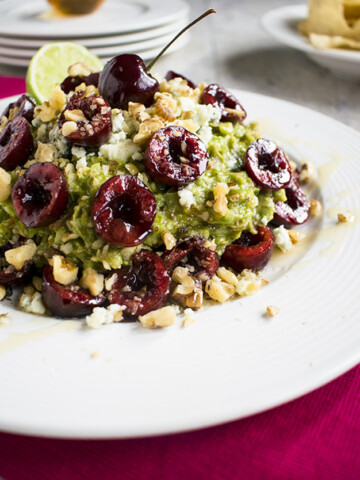 close-up of guacamole with cherries, gorgonzola and walnuts in a bowl