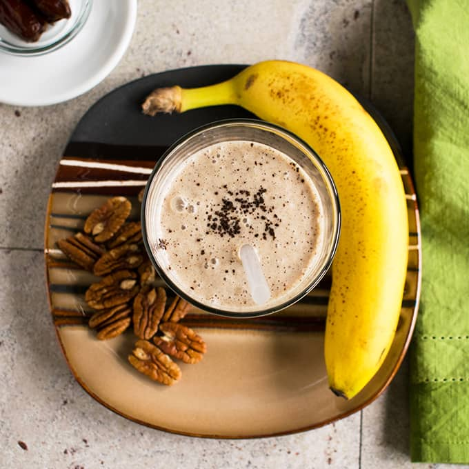 overhead view of glass of homemade vanilla frappuccino on a plate with bunch of pecans and banana