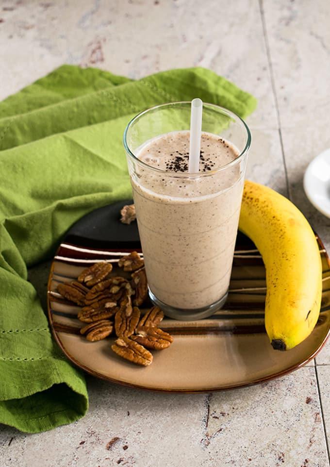 healthy homemade vanilla frappuccino, banana, pecans on a plate with napkin