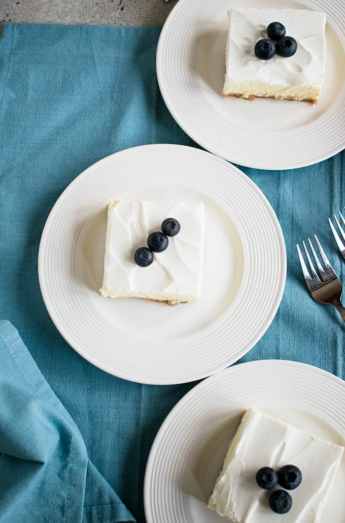 overhead view of three plates of cheesecake with sour cream topping and blueberries