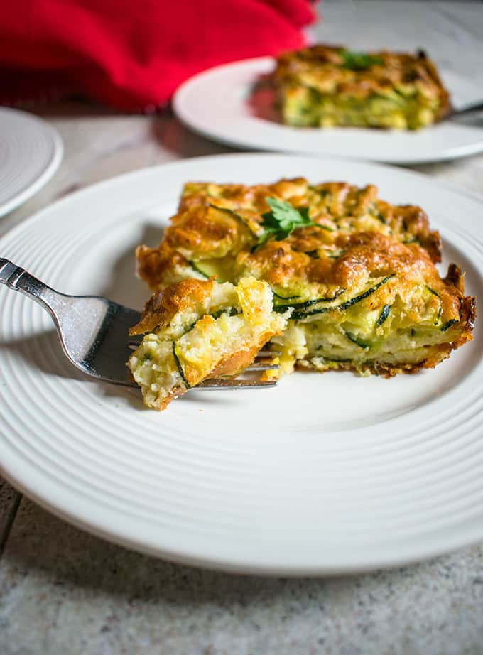A plate of zucchini casserole with a forkful of food