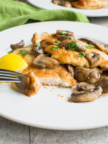 chicken marsala with mushrooms on a plate with a fork