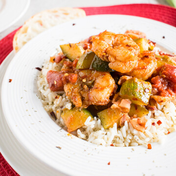 Shrimp stew with bacon, zucchini, tomatoes and rice in a bowl