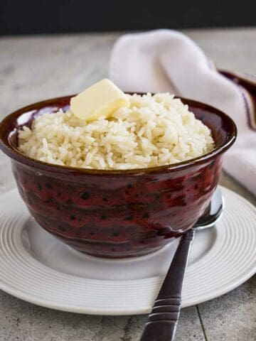 bowl of long-grain rice with butter in a bowl on a plate with spoon