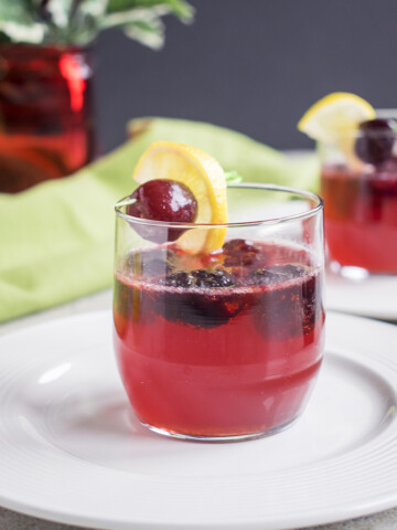 a glass of dark cherry amaretto sour with a cherry and lemon garnish