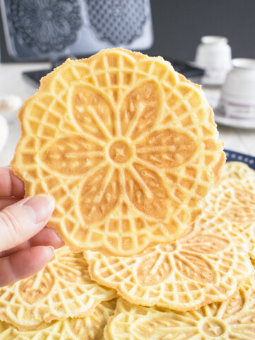 hand holding an almond pizzelle cookie