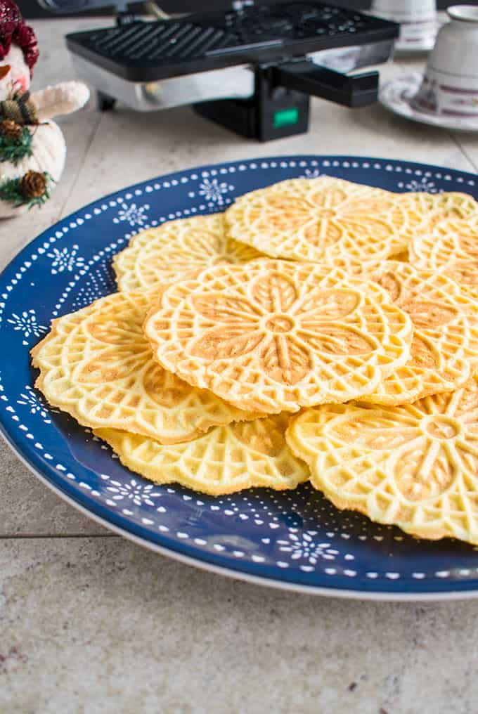 close-up photo of almond pizzelle cookies covering a plate