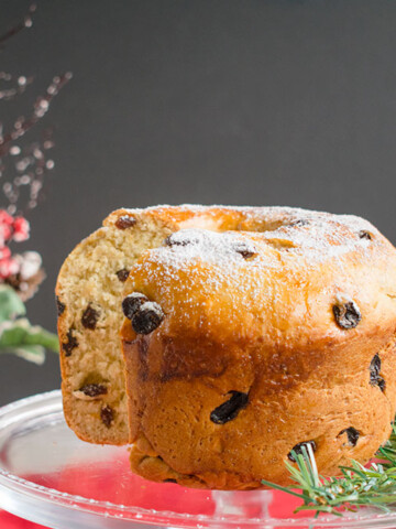 panettone bread with a slice cut out on a cake stand