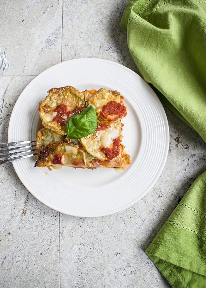 overhead photo of a slice of eggplant parmigiana on a plate with a fork