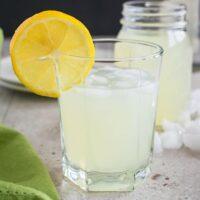 glass of lemonade moonshine with a lemon garnish in front of a jar of lemonade moonshine