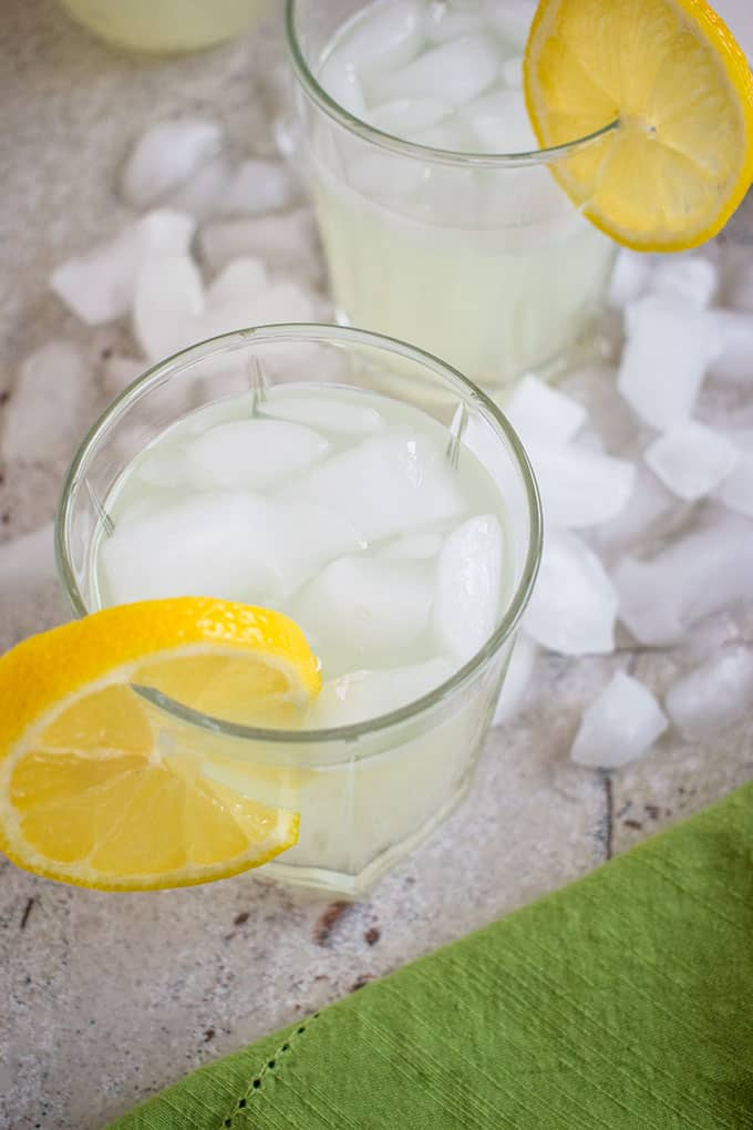 overhead view of two glasses of lemonade moonshine with lemon garnish surrounded by ice cubes