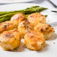 close-up photo of broiled scallops with parmesan bread crumbs in front of asparagus on a plate