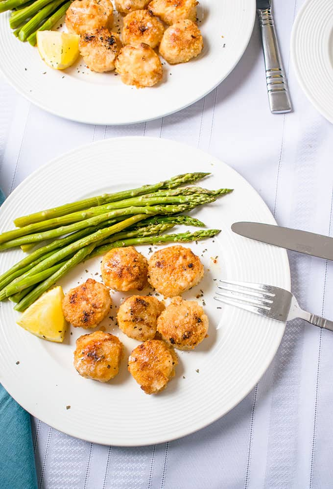 Plate with broiled scallops with parmesan bread crumbs, asparagus and a lemon wedge with a fork and knife