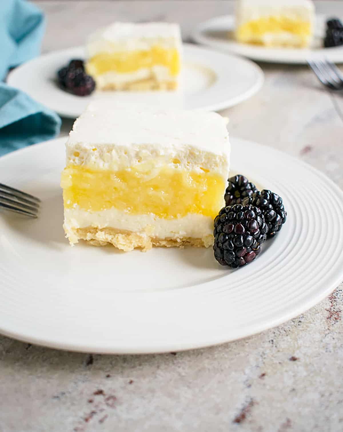 slice of lemon lush on white plate with fork and blackberries
